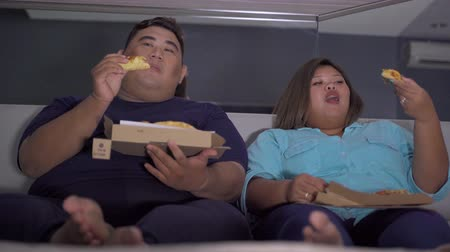 Overweight man speaking with his wife while eating and watching TV on the bedroom at home. Shot in 4k resolution Wideo