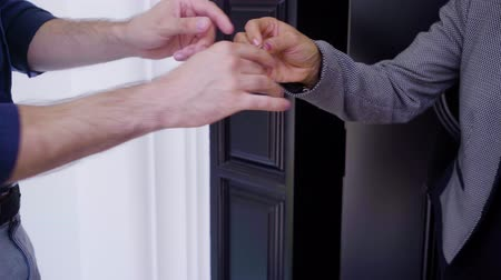 Hands of a female realtor shaking hand with her client while giving a key of new house. Shot in 4k resolution
