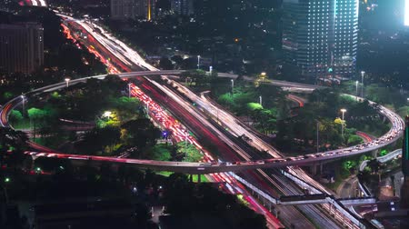 sudirman : JAKARTA, Indonesia - January 28, 2020: Beautiful timelapse of light trails on Semanggi bridge and skyscrapers view at night time in Jakarta city. Shot in 4k resolution