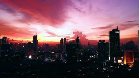 szemléltető : JAKARTA, Indonesia - January 30, 2020: Beautiful aerial view of twilight sky with silhouette of skyscrapers in Jakarta city. Shot in 4k resolution from a drone flying upward