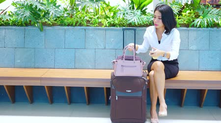 Beautiful businesswoman doing makeup while sitting on bench with luggage in train station. Shot in 4k resolution