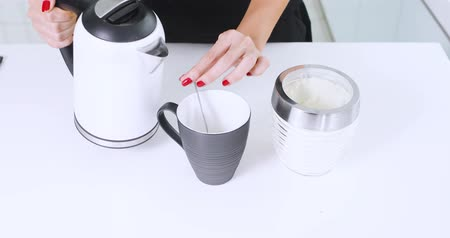 Hands of young woman making a cup of hot milk on the table in the kitchen. Shot in 4k resolution Wideo