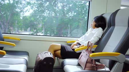 train workers : Side view of tired businesswoman sleeping in the airport train while leaning on the window. Shot in 4k resolution Stock Footage