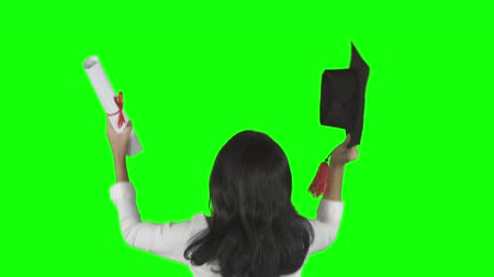 Back view of female student celebrating her graduation while raising a graduation cap and diploma. Shot in 4k resolution with green screen background