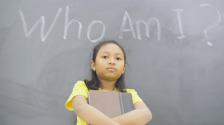 Female elementary school student holding a book while standing with text of who am i? in the classroom. Shot in 4k resolution Wideo