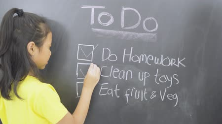 Little girl making to do list on the chalkboard while putting mark on checkboxes. Shot in 4k resolution Wideo