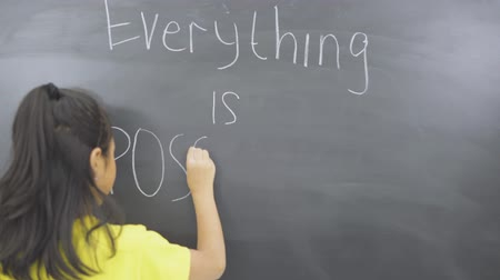 Rear view of little girl writing text of Everything is Possible on the chalkboard in the classroom. Shot in 4k resolution Wideo