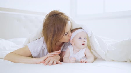Beautiful mother kissing her baby girl while lying together under a blanket in the bedroom at home. Shot in 4k resolution