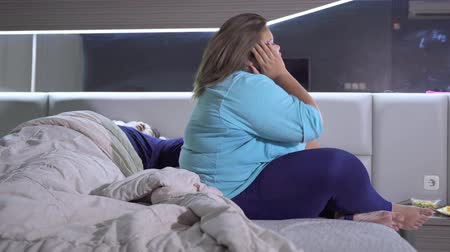 Stressful obese woman sitting on the bed side while her husband sleeping. Shot in 4k resolution