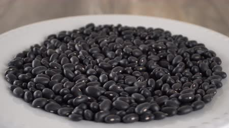 placas : Black beans rotating on a white plate. Seamless loopable.