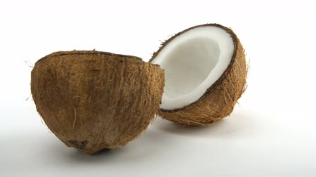 rehydration : Ripe tropical coconut split in two halves rotating on a white background. Exotic fruits, loopabe. Stock Footage