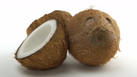 rehydration : Ripe tropical coconut and two coconut halves rotating on a white background. Loopable exotic fruits. Stock Footage