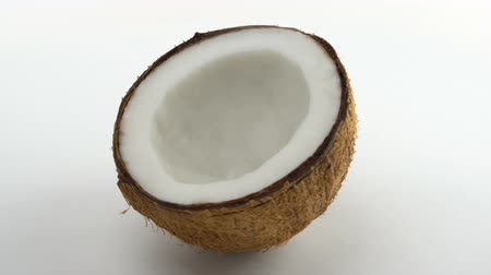 rehydration : One half of a ripe tropical coconut rotating on a white background. Tropical fruits. Loopable. Stock Footage