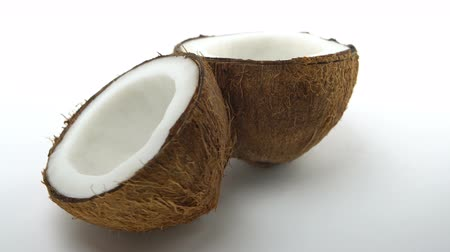 rehydration : Ripe tropical coconut split in two halves rotating on white background. Looping exotic fruits. Stock Footage