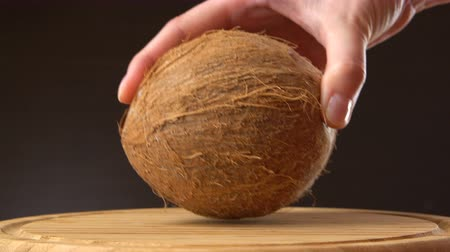 rehydration : Female hand puts ripe tropical coconut on a wooden table against black background. Tropical fruit.