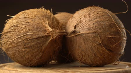 rehydration : Three ripe tropical coconuts rotating on a wooden table against black background. Loopable. Stock Footage