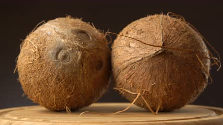 rehydration : Two ripe tropical coconuts rotating on a wooden table against black background. Loopable. Stock Footage