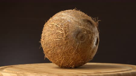 rehydration : Ripe tropical coconut rotating on a wooden table against black background. Tropical fruits, loopable Stock Footage