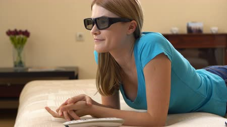 novela : Beautiful attractive young woman in blue t-shirt lying on sofa and watching TV in 3D-glasses.