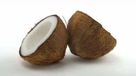 rehydration : Ripe tropical coconut split in two halves rotating on a white background. Tropical fruits, loopable. Stock Footage