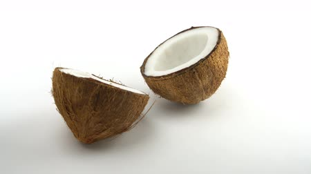 rehydration : Tropical ripe coconut split in two halves rotating on a white background. Tropical fruits, looped.