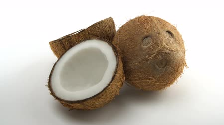 rehydration : Ripe tropical coconut and two halves of coconut rotating on a white background. Tropical fruits, loopable. Stock Footage