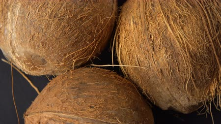 rehydration : Three ripe tropical coconuts rotating on a black background. Tropical fruits and food concept. Loop, Stock Footage
