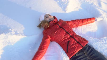 snow angel : Beautiful young woman making snow angel in a winter park, having silly fun, smiling. Slow motion.