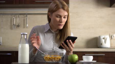 phablet : Beautiful young attractive businesswoman having cornflakes for breakfast and using her smartphone. Stock Footage