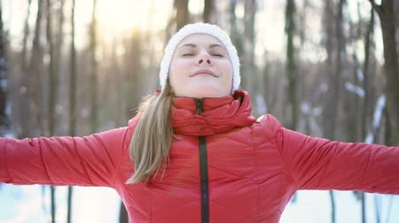 dech : Beautiful young woman standing in winter park, smiling, taking a deep breath. Slow motion video. Dostupné videozáznamy