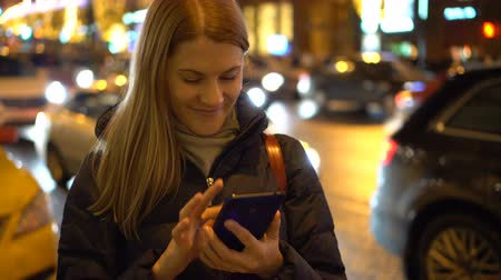 rua : Beautiful attractive young woman standing in a street and using her smartphone. City lights Cars.