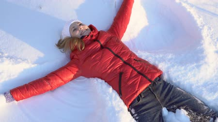 snow angel : Attractive young woman making snow angel in a winter park, having silly fun, smiling. Slow motion. Stock Footage