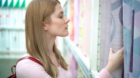 продукты : Beautiful attractive young woman selects wall-paper on the shelves in the store. Consumerism concept.