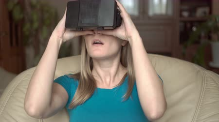 vay : Modern casual woman in blue t-shirt sitting in chair at home. Using her virtual reality glasses.
