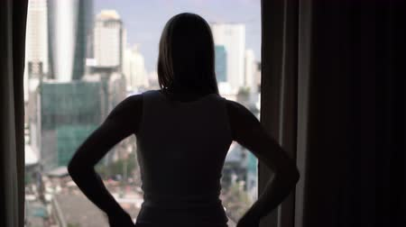 unveil : Silhouette of woman unveiling curtains and looking out of window. City skyscrapers landscape outside