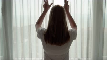 unveil : Woman in white t-shirt unveiling curtains and looking out of window. Enjoying the sea view outside