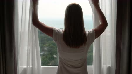 window room : Woman in white t-shirt unveiling curtains and looking out of window. Enjoying the sea view outside