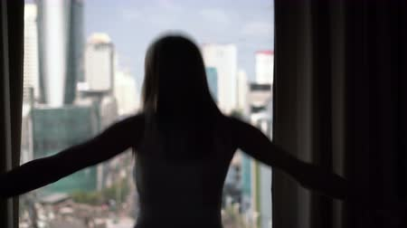 unveil : Silhouette of woman unveiling curtains and having fun jumping. City skyscrapers landscape outside
