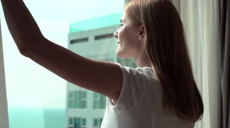 unveil : Young woman in white t-shirt opening curtains and looking out of window enjoying the sea view. Stock Footage