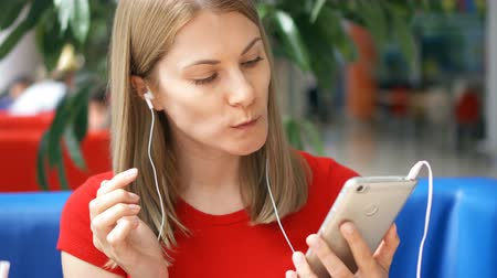 famished : Young hungry famished woman in red t-shirt sitting in cafe listening music on smartphone with ear-phones eating french fries
