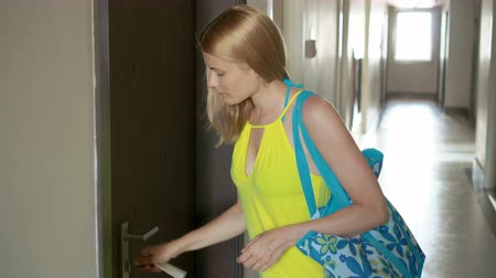 фронт : Beautiful young woman in yellow dress closing the door of her apartment with keys and walking away Стоковые видеозаписи