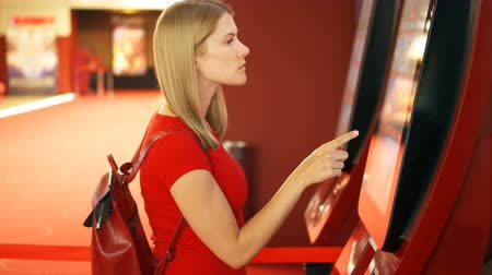 vending machine : Young pretty woman in red t-shirt choosing movie and buying ticket from vending machine at movie theater