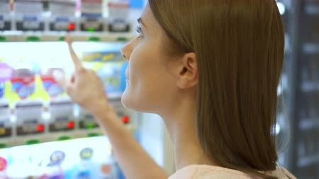 vending machine : Beautiful hungry woman picking item out of vending machine in mall. Choosing unhealthy snacks being famished
