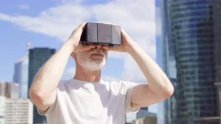 пенсионер : Senior bearded man standing in downtown business district using VR glasses. Skyscrapers on background Стоковые видеозаписи