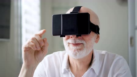 double happiness : Good-looking handsome senior man in white using VR 360 glasses at home. Making browse, zoom and tap gestures. Concept of active modern elderly people, learning to use contemporary technologies. Stock Footage