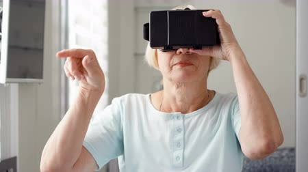 double happiness : Good-looking blond senior woman in white using VR 360 glasses at home. Making browse, zoom and tap gestures. Concept of active modern elderly people, learning to use contemporary technologies. Stock Footage