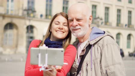 alma : Young daughter taking selfie photo on mobile with her senior father on vacation trip in Paris in Place Vendome. Happy family enjoying vacation.