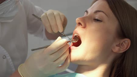 perfuração : Dentist treating teeth to woman patient in clinic. Female professional doctor stomatologist at work. Dental equipment on background. Dental check up