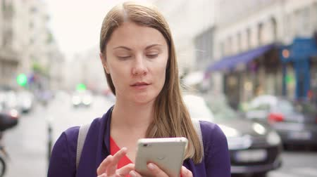 looking : Positive businesswoman standing on street using mobile. Professional female browsing reading news, chatting with friends. European street on background