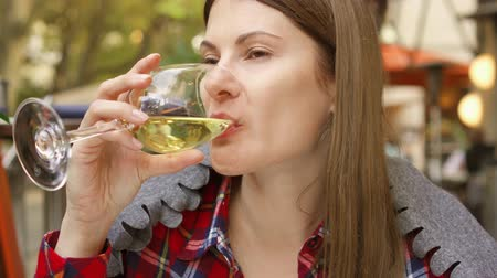 pléd : Woman sitting in street cafe drinking white wine from glass. Smiling beautiful thirsty female at outdoor restaurant with gray plaid on her shoulders Stock mozgókép